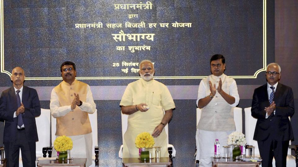 Prime Minister Narendra Modi launches the Sahaj Bijli Har Ghar Yojana or Saubhagya, to supply electricity to poor households, in New Delhi on Monday. Petroleum Minister Dharmendra Pradhan and Power Minister RK Singh are also seen.