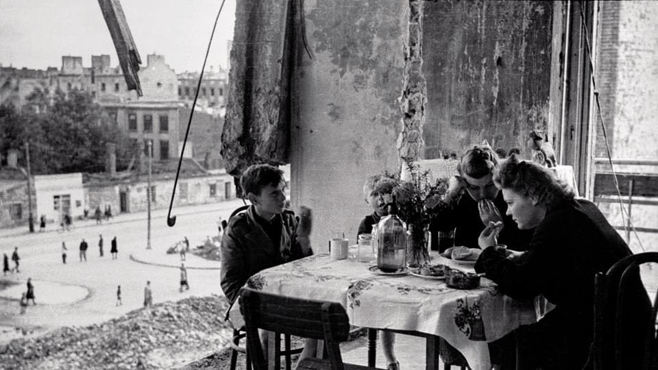 Warsaw 1945. The everyday life of Warsaw people remained in ruins after the war — here a family is seen eating at their battered home.