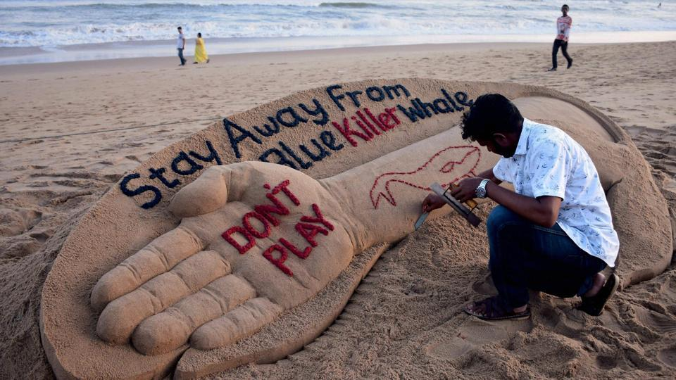 "Sand artist Sudarsan Pattnaik creates a sand sculpture with message ""Stay away from Blue Killer Whale : Don't Play"" at Puri beach in Odisha on Monday."