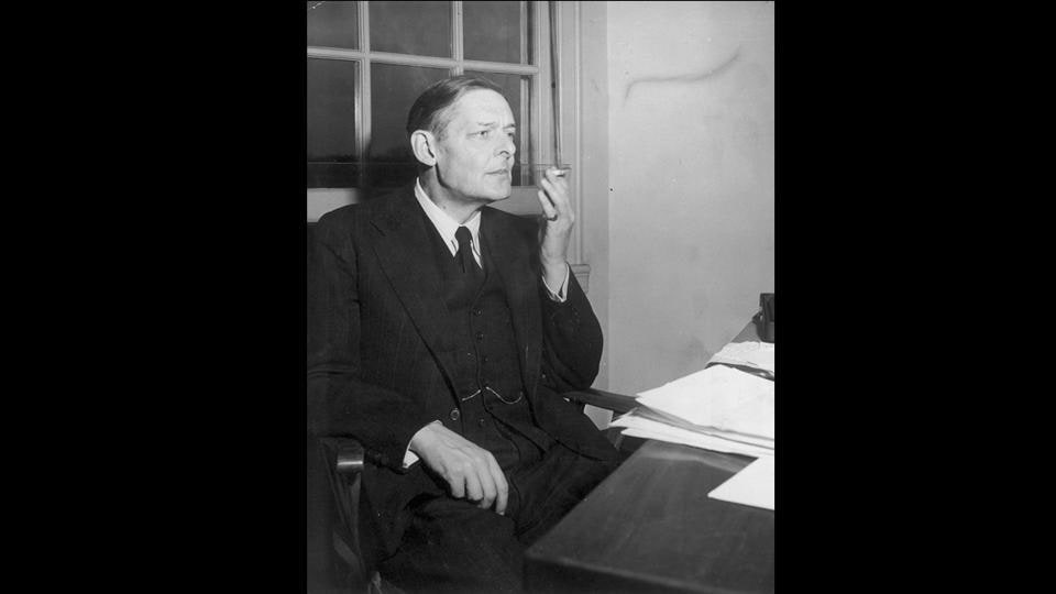 Writer T.S. Eliot (1888 - 1965) takes a reflective puff at a cigarette before starting work, November 17, 1948. (Keystone Features / Getty Images)