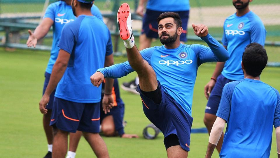 Indian cricket team captain Virat Kohli tries an acrobatic kick while playing football during a practice session ahead of the fourth One Day International (ODI) match against Australia cricket team at the M Chinnaswamy Stadium in Bangalore on Tuesday.