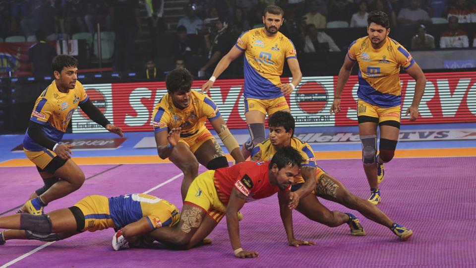 Tamil Thalaivas players try to pin down Gujarat Fortunegiants' player Chandran Ranjit, in red, during their Vivo Pro Kabaddi league match in New Delhi, India, Tuesday, Sept. 26, 2017.
