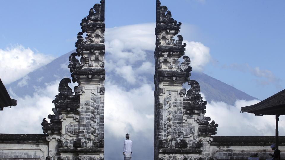 Balinese man watches Mount Agung volcano almost covered with clouds as he stands at a temple in Karangasem, Bali, Indonesia, Tuesday, September 26.