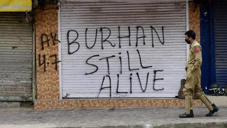 Srinagar: A policeman walks out side closed shops during restriction and strike in Srinagar. Authorities had imposed restrictions in most parts of Valley following the killing of Burhan Wani