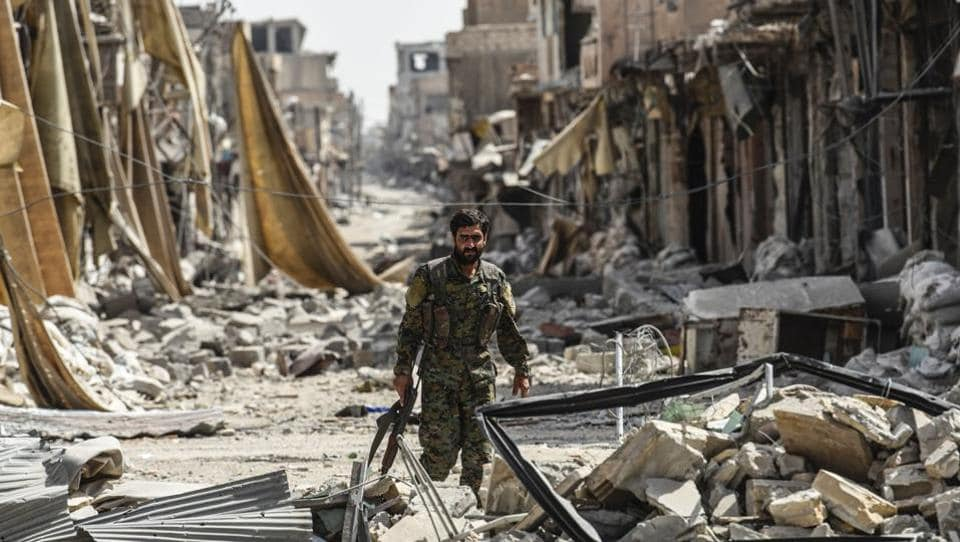 A member of the Syrian Democratic Forces (SDF) walks through debris on the eastern frontline of Raqqa on September 25, 2017. Syrian fighters, backed by US Special Forces, are battling to clear the last remaining Islamic State (IS) fighters holed up in their crumbling stronghold of Raqqa. 'We control 80% of Raqqa and the other 20% is in the firing line of our forces,' said Jihan Sheikh Ahmed, spokeswoman for the 'Wrath of the Euphrates' campaign. (Bulent Kilic / AFP)