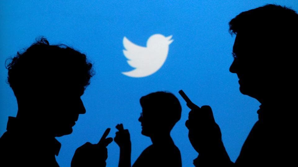 People holding mobile phones are silhouetted against a backdrop projected with the Twitter logo in this illustration picture.