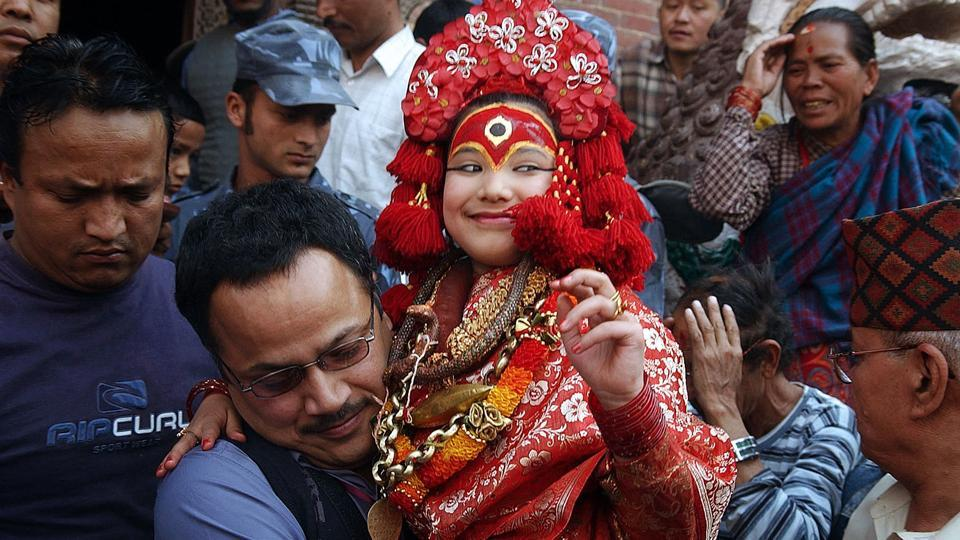 "File photo taken on March 29, 2006 shows a priest carrying Nepal's Living Goddess 'Kumari Devi' (centre) during the Ghode Jatra festival in Kathmandu. A three-year-old girl has been named the new Kumari of Nepal's capital Kathmandu after her predecessor retired when she reached puberty, continuing an ancient tradition that sees young girls worshipped as ""living goddesses""."