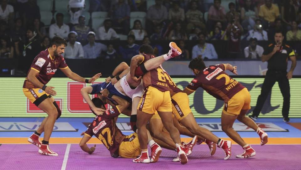 UP Yoddha players pin down Dabang Delhi player Abolfazl Maghsodlou, in blue jersey, during their Pro Kabaddi League match in New Delhi on Wednesday.