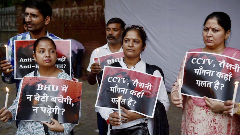 People display placards during a candle light vigil to condemn the police lathicharge on the female students of Banaras Hindu University (BHU), in New Delhi on Tuesday.