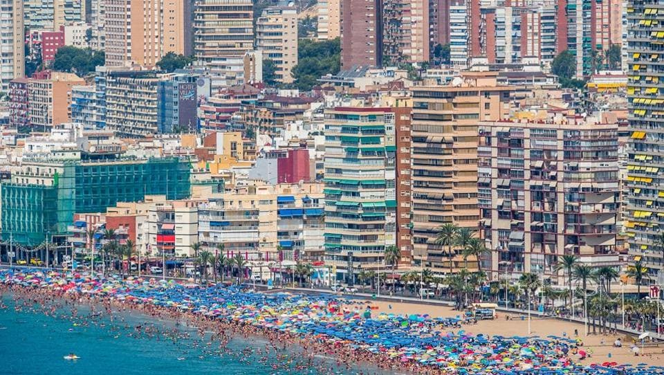 People sunbathe on Levante beach in Benidorm, Spain. A tiny fishing village till the 1960s, it's now a popular Mediterranean holiday destination known for its nightlife.  (David Ramos / Getty Images)