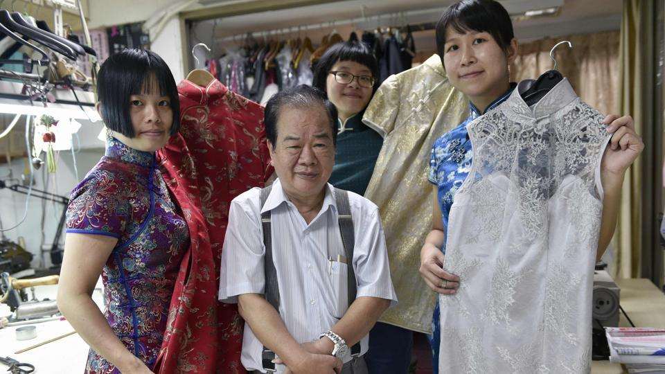 Taiwanese 'qipao' maker Lin Chin-te (C) and his students posing for photos at his studio in Taipei. Lin Chin-te, 74, is among a handful of craftsmen in Taiwan who still specialise in handmaking the high-collar, figure-hugging garment which was once part of many women's daily wardrobes.