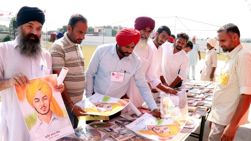 People looking at posters of Bhagat Singh on his birth anniversary at a book stall during conference of Revolutionary Marxist Party of India in Bathinda on Thursday. (Sanjeev Kumar/HT)