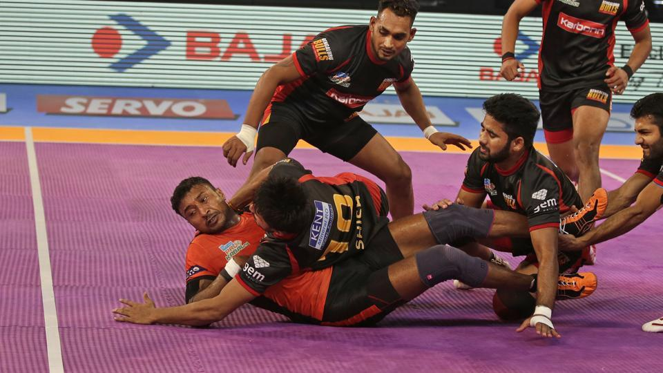 U Mumba raider Kashiling Adake (left) successfully breaks loose from the grip of Bengaluru Bulls players to score a point during their Pro Kabaddi League (PKL)match in New Delhi on Thursday.