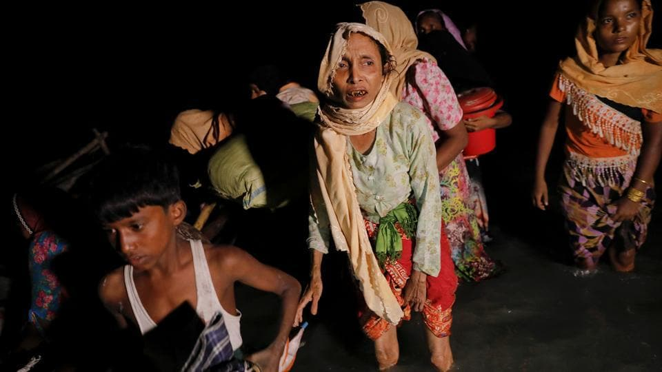 Women and children make their way to the shore as hundreds of Rohingya refugees arrive under the cover of darkness by wooden boats from Myanmar to Shah Porir Dwip, in Teknaf, near Cox's Bazar in Bangladesh, September 27.