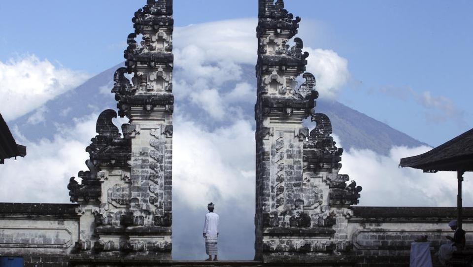 A Balinese man looks on from a temple in Karangasem as Mount Agung volcano is shrouded in clouds. The National Disaster Mitigation Agency's command post in Bali said the number of evacuees has swelled to about 134,200 by Thursday evening fearing it will soon erupt. This is more than double the estimated population within the immediate danger zone, as people farther from the mountain join those fleeing. (Firdia Lisnawati / AP)
