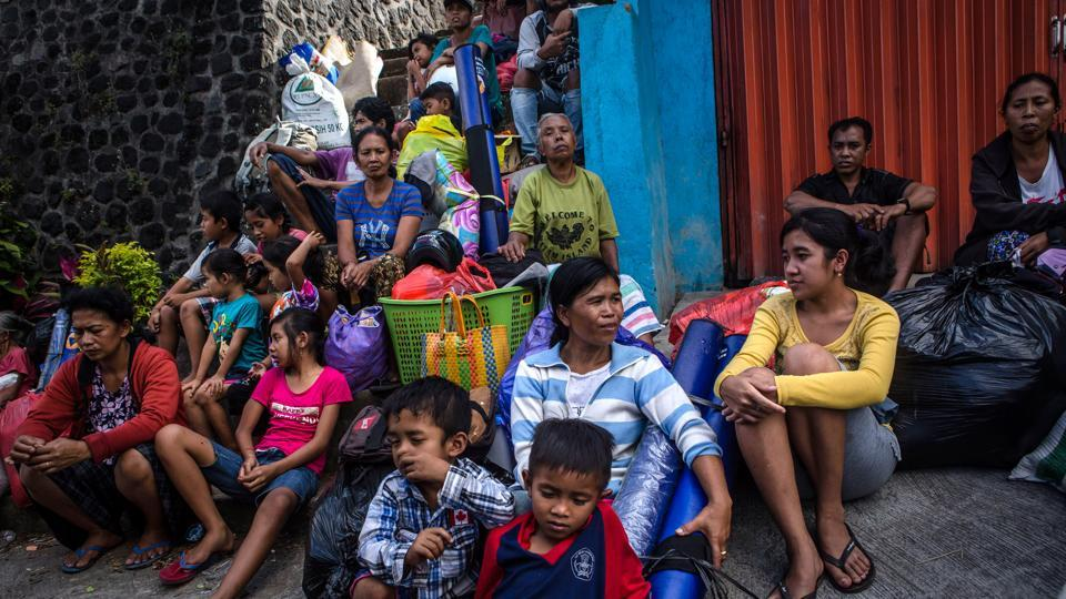 People await transportation to a temporary shelter at Sibetan village on September 28, 2017 in Karangasem regency. Volcanologists say the escalation in tremors indicates an eruption is more likely than not, but they can't say with certainty when. Tectonic plates carry massive quantities of rock deep into the earth which melt into magma. The magma that feeds Mount Agung traps more gas, producing larger eruptions. (Ulet Ifansasti / Getty Images)