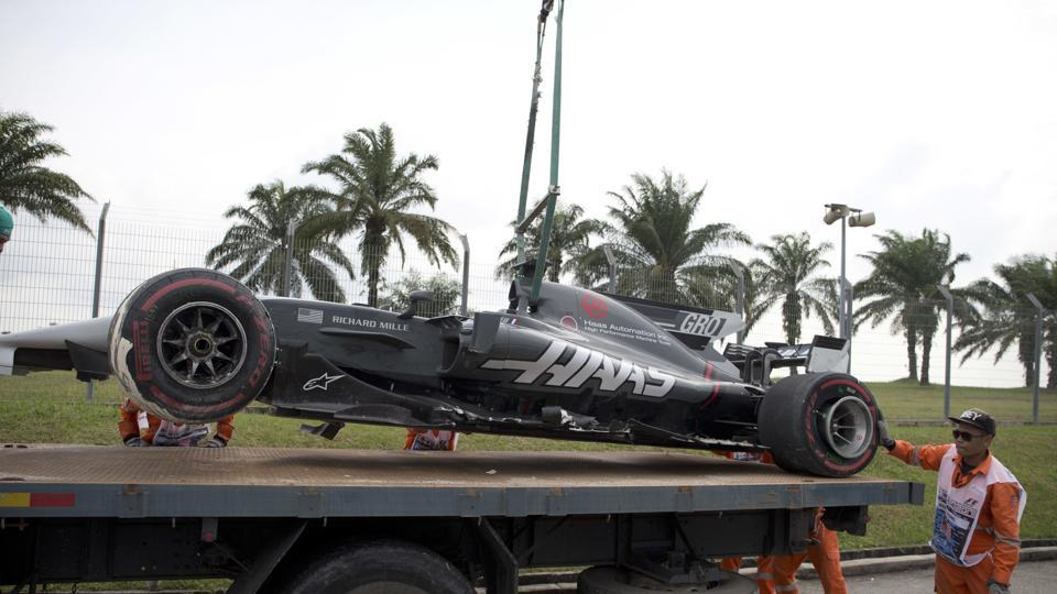 Sepang Circuit track crew lifts Haas driver Romain Grosjean's car after it crashed out during the second free practice of the Formula One (F1) Malaysian Grand Prix on Friday.