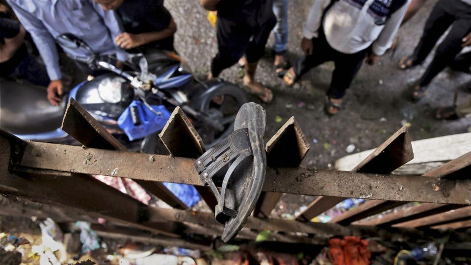 A slipper of an injured commuter is seen stuck on the railing of a pedestrian bridge where a stampede took place at the Elphinstone station in Mumbai on Friday.