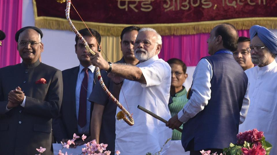 Prime Minister Narendra Modi with President Ram Nath Kovind holds a bows and arrow during Dussehra celebrations at Parade Ground in New Delhi on Saturday.