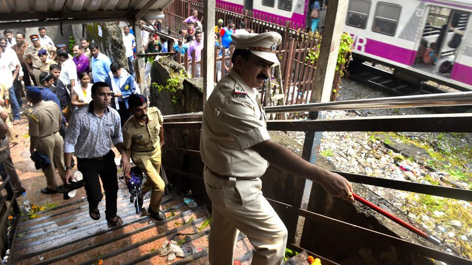 Police officers investigate the foot overbridge after stampede at Elphinstone Railway station in Mumbai, on September 29, 2017.