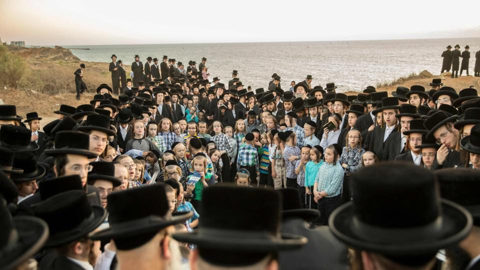 Orthodox Jewish men pray along the Mediterranean Sea in the Israeli city of Herzliya, near Tel Aviv, while performing the 'Tashlich' ritual on September 28, 2017, during which 'sins are cast into the water to the fish'. The 'Tashlich' ritual is performed before the Day of Atonement, or Yom Kippur, the most important day in the Jewish calendar, which in 2017 began at sunset on September 29. (Jack Guez / AFP)