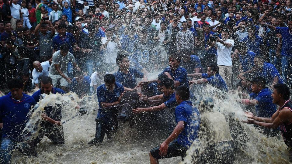 Nepali Hindu devotees splash water on a buffalo set to be sacrificed during the Hindu Dashain Festival in Bhaktapur, on the outskirts of Kathmandu, on September 29, 2017. Dashain is the longest and the most auspicious festival in the Nepalese calendar and celebrates the triumph of good over evil.  (Prakash Mathema / AFP)