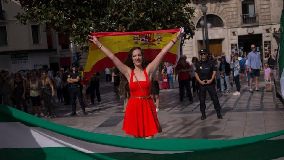 A woman holds a Spanish flag as she confronts demonstrators in support of the referendum in Catalonia on October 01, 2017, in Granada. (JORGE GUERRERO/AFP Photo)