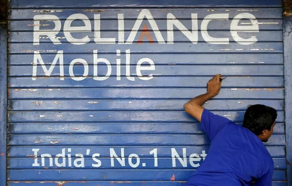 A man opens the shutter of a shop painted with an advertisement of Reliance Communications in Mumbai.