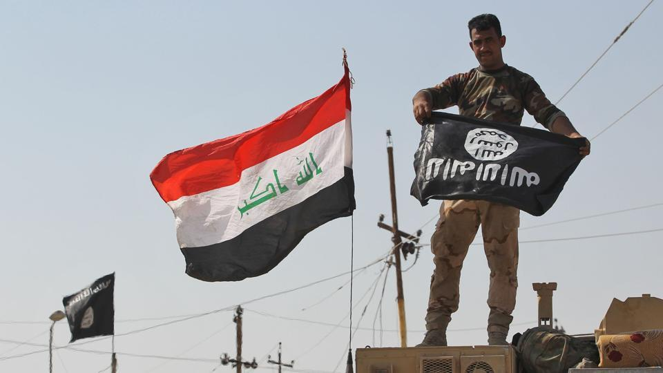A member of the Iraqi forces holds the Islamic State flag upside down after ousting the jihadists from Sharqat  town on September 22, 2017.