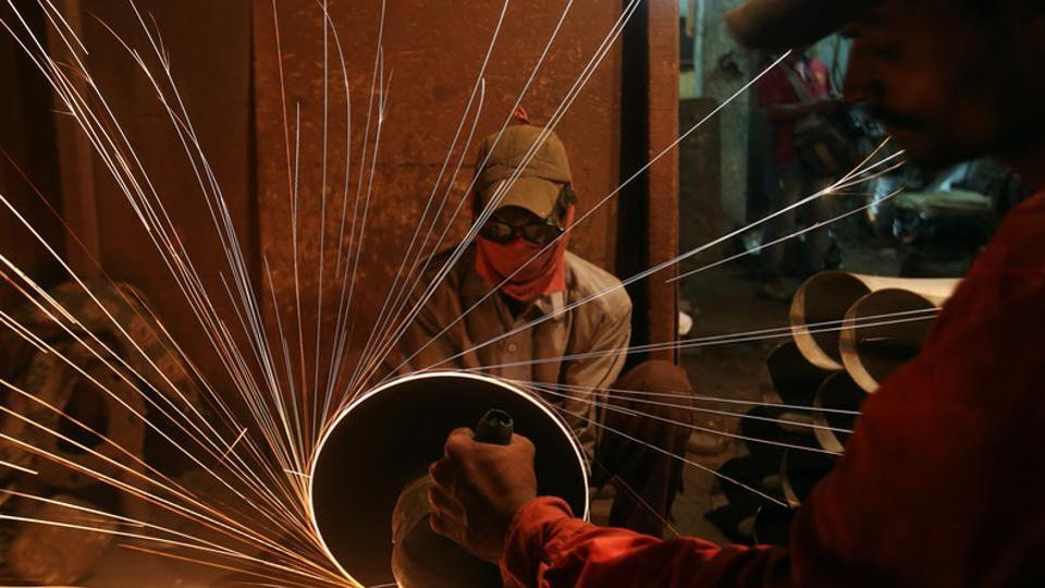 A worker cuts metal inside a workshop manufacturing metal pipes in Mumbai.  India's manufacturing industry can largely be divided into a limited number of large-sized firms and a preponderance of small, household enterprises, with a gaping hole in the middle.