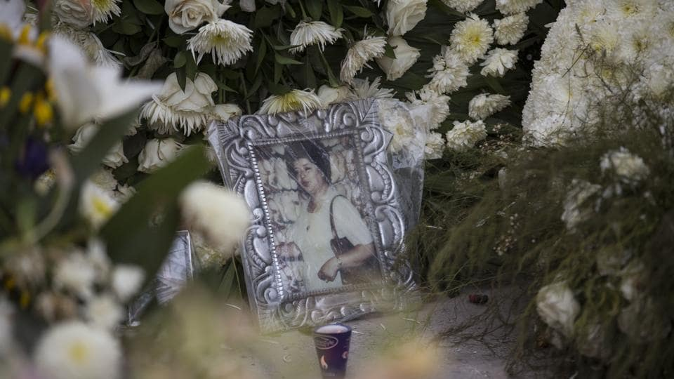 A framed portrait of an unidentified woman and bouquets of white flowers make up part of a memorial at the site of an apartment building at the corner of Division del Norte and Peten, in Mexico City. The seven-story apartment building was felled by the Sept. 19 earthquake, killing several people. (Moises Castillo / AP)