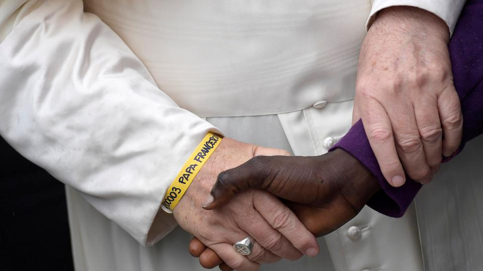 Pope Francis wears a yellow plastic ID bracelet as he shakes hand with a man during a visit to a migrant's reception centre in Bologna, Italy, on Sunday.