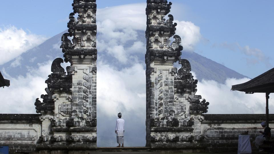 A man watches the Mount Agung volcano from a temple in Karangasem, Bali, Indonesia, on Tuesday, Sept. 26, 2017. A week after authorities announced a high alert, tremors that indicate an eruption is coming show no sign of abating, swelling the exodus from the region to at least 140,000 people. (Firdia Lisnawati / AP)