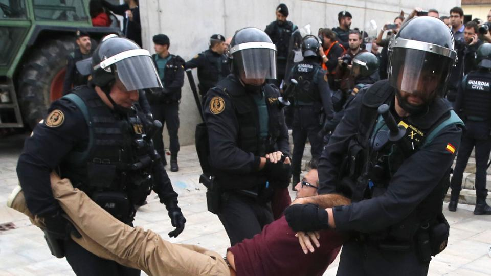 Spanish Guardia Civil guards drag a man outside a polling station in Sant Julia de Ramis, where Catalan president was supposed to vote. (RAYMOND ROIG/AFP PHOTO)