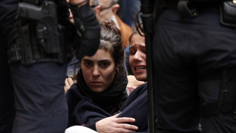 Two girls sit on the pavement after the arrival of Spanish police officers at a polling station in Barcelona, on October 1, on the day of a referendum on independence for Catalonia banned by Madrid.