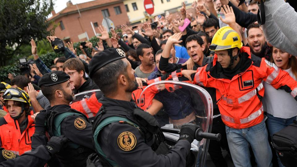 Firemen try to hold a group of people in front of Spanish Guardia Civil officers outside a polling station in San Julia de Ramis. (Lluis Gene/AFP Photo)
