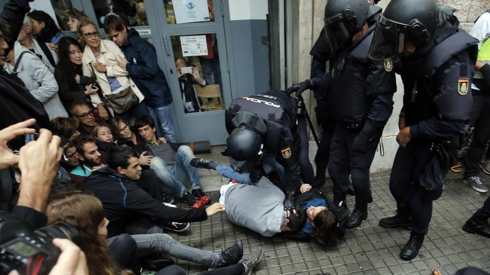 Spanish police officers immobilize two people outside a polling station in Barcelona, on October 1, 2017, on the day of a referendum on independence for Catalonia banned by Madrid. More than 5.3 million Catalans are called today to vote in a referendum on independence, surrounded by uncertainty over the intention of Spanish institutions to prevent this plebiscite banned by justice.  (PAU BARRENA/AFP Photo)