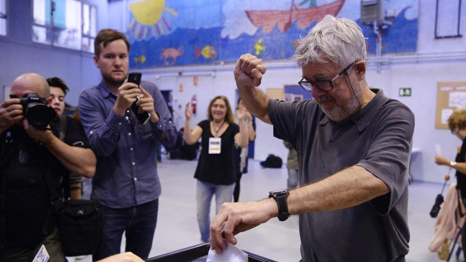 A man raises his fist as he casts his ballot in a polling station in Barcelona. (AFP Photo)