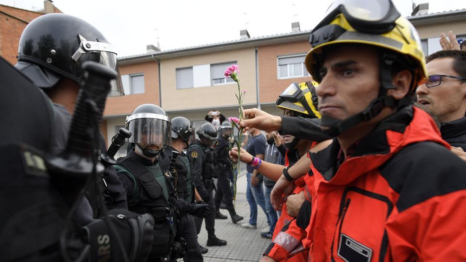 A person gives a carnation to Guardia Civil officers as firemen hold the people in front of Spanish Guardia Civil officers outside a polling station in San Julia de Ramis, on October 1, 2017, on the day of a referendum on independence for Catalonia banned by Madrid. (AFP Photo)