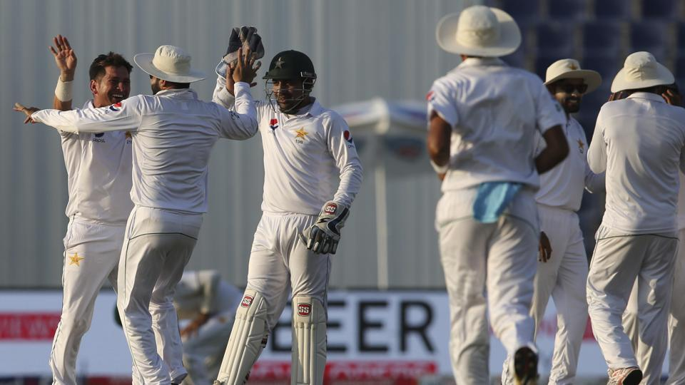 Pakistan's Yasir Shah celebrates with his teammates after dismissing Sri Lanka's Dinesh Chandimal during the fourth day of the first Test in Abu Dhabi on Sunday.