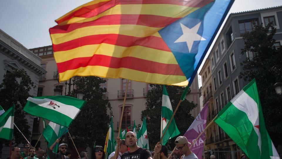 People hold Andalusian and Catalan pro-independence 'Estelada' flags during a demonstration in support of the referendum in Catalonia, in Granada.