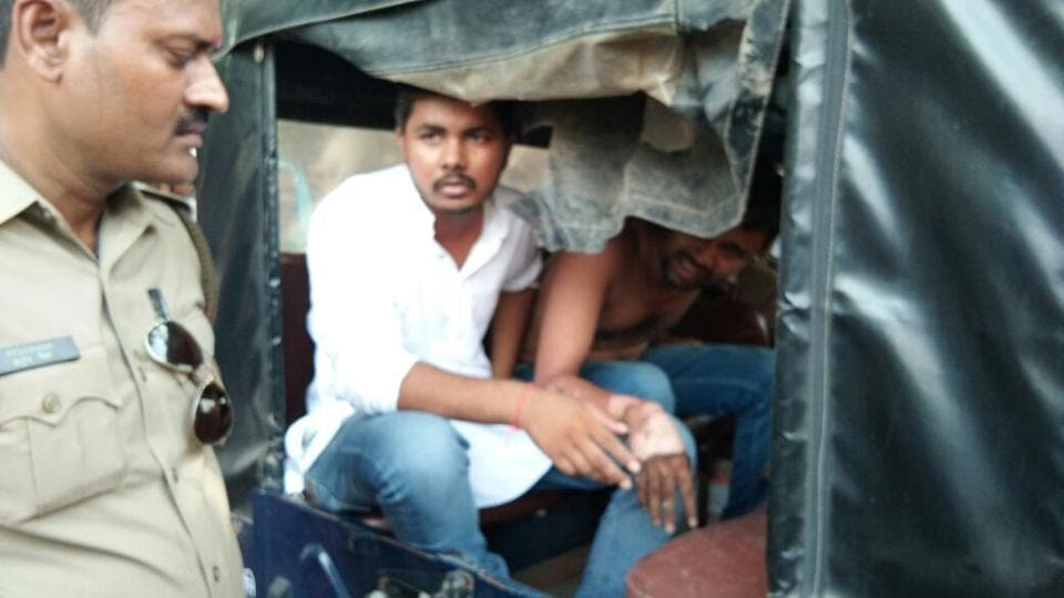 Avinash Anand, who tried to immolate himself, with a friend in police custody.