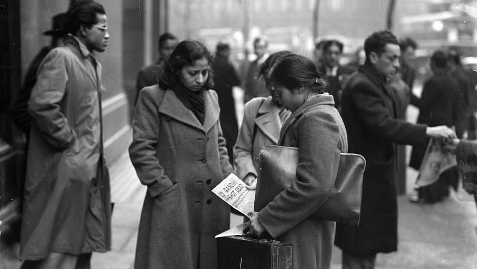 Young women seen reading a newspaper among members of London's Indian and Pakistani population outside India House, central London, after hearing of the assassination of the Indian statesman and advocate of non-violence, Mahatma Gandhi in 1948. ( Reg Speller / Fox Photos / Getty Images)