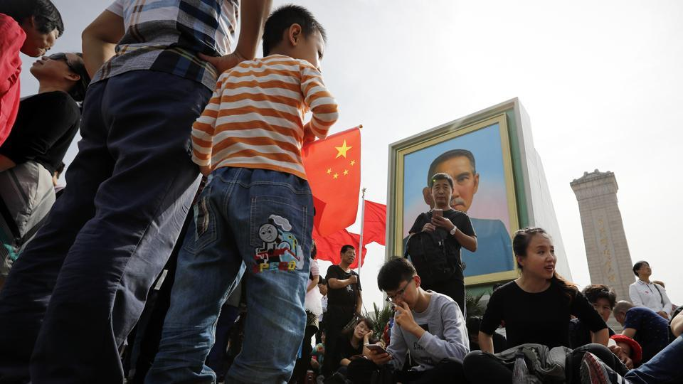 Visitors rest near a portrait of Sun Yat-sen at Tiananmen Square, China. Widely regarded as the 'Father of Nation' in the Republic of China (ROC), Sun Yat-sen served as the nation's first president known to have played an instrumental role in overthrowing the Quin Dynasty.  (Andy Wong / AP)