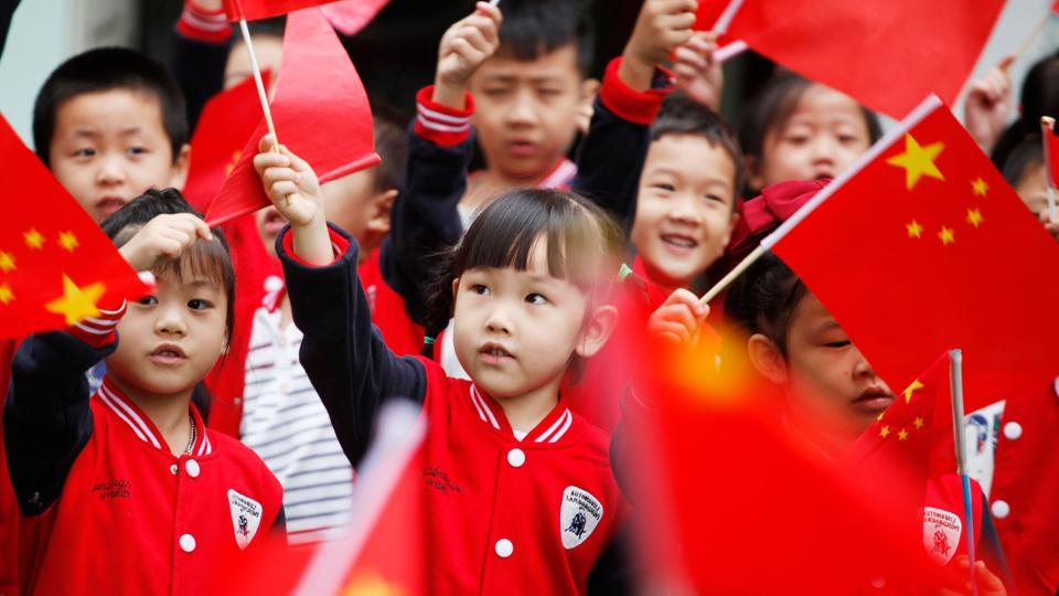 Children wave national flags as they sing revolutionary songs to celebrate the National Day at a kindergarten in Tonglu, China. (AFP)