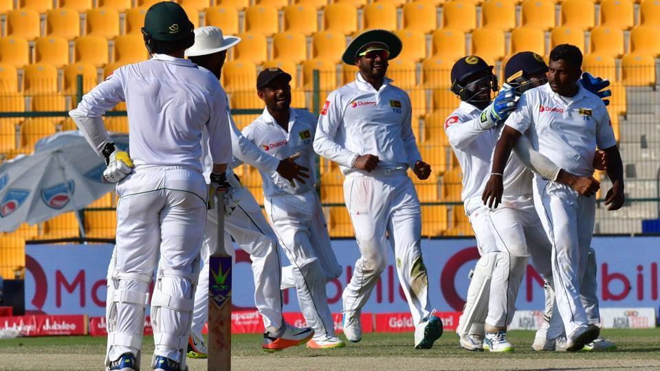 Sri Lanka's Rangana Herath (R) celebrates after dismissing Pakistan's Mohammad Amir on the fifth day of the first cricket Test at Sheikh Zayed Stadium in Abu Dhabi on October 2, 2017.