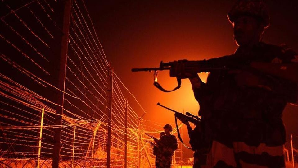 Border Security Force soldiers patrol along a border fence at an outpost along the Line of Control (LOC) between India-Pakistan at Abdulian, some 38 kms southwest of Jammu.