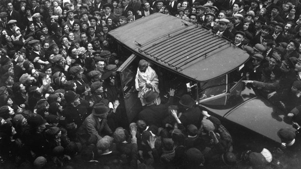 An admiring East End crowd gathered to witness the arrival of Mahatma Gandhi in Canning Town, East London, as he called upon Charlie Chaplin in 1931. Gandhi was in England in his capacity as leader of the Indian National Congress attending the London Round Table Conference on Indian constitutional reforms. (London Express / Getty Images)