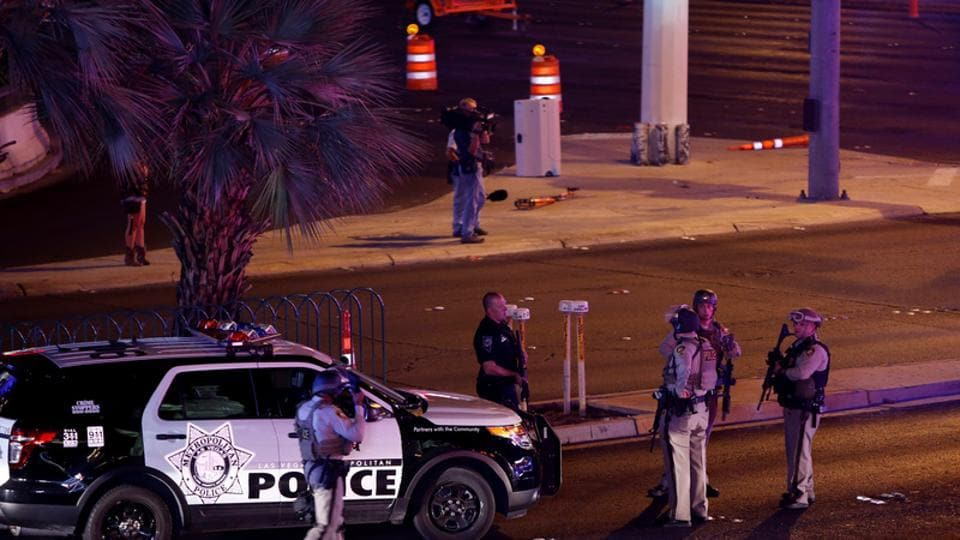 Las Vegas Metro Police officers gather near the intersection of Tropicana Avenue and Las Vegas Boulevard South after a mass shooting at a music festival.