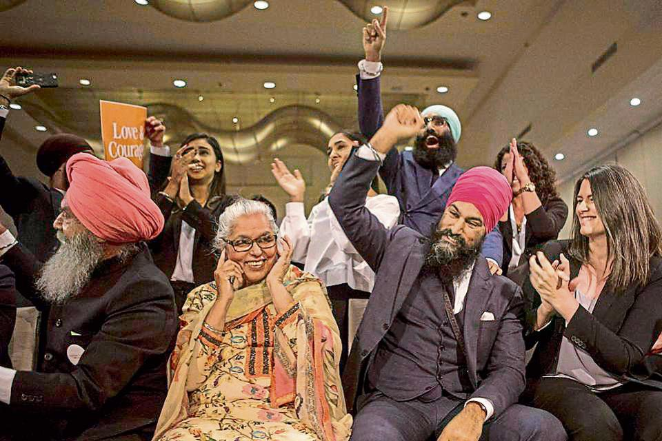 Jagmeet Singh flanked by mother Harmeet Kaur and father Jagtaran Singh (left) and campaign manager Michal Hay (right) as it's announced he has won the first ballot in the contest for leader of the leftist New Democrat party in Toronto.